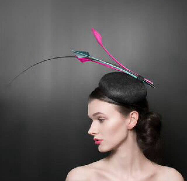 Black button beret with black quill, and striking pink arrow feathers