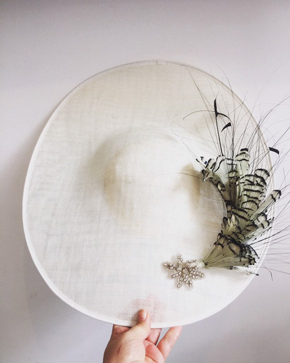 Large white saucer hat with spray of black and white feathers and dimonte motif