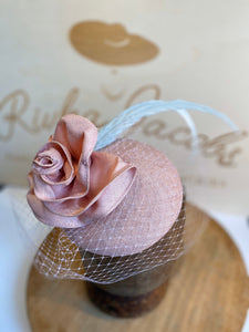 Pink rose hat/fascinator, with white veil, pink strae rose to match base and light green feathers. rivka jacobs millinery. hats uk devon