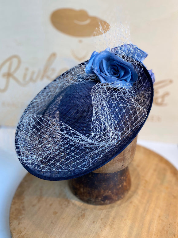 Navy blue saucer hat with light blue flowers and veiling.
