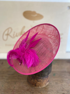 Shocking pink saucer hat with a big spray of pink feathers