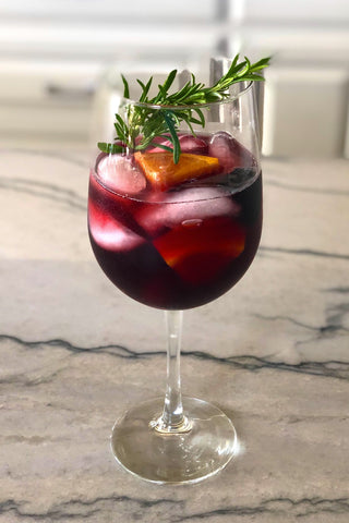 Delicious red sangria featuring oranges, blackberries, cherries and rosemary