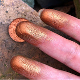 finger swatch of copper eyeshadow in front of some rocks