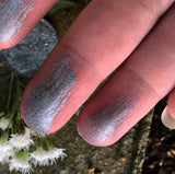 swatches of gun metal grey eyeshadow on fingertips in front of a baby's breath flower