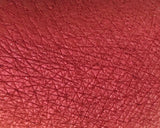 Swatch of red eyeshadow pigment on arm satin finish