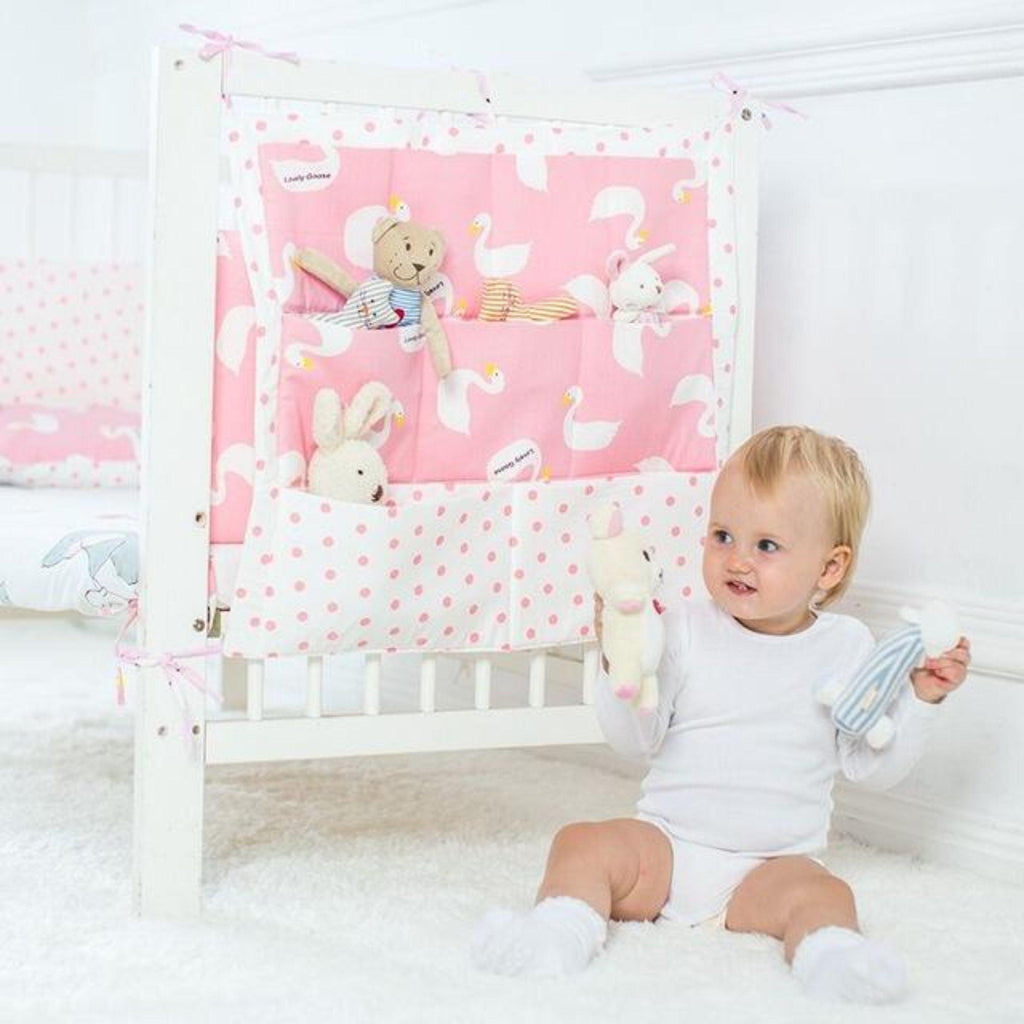 Pink and white printed swan crib organizer with self ties for storage of toys diapers