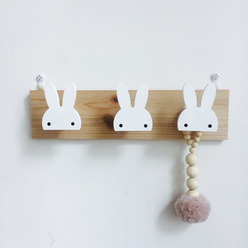 Three little wood bunny head and ears wall hooks mounted on a pine wood rectangle piece