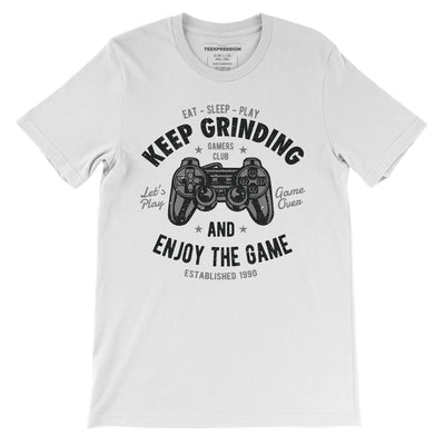 Keep grinding and enjoy the game written with illustration of a gaming controller on white t-shirt for both men and women from Teexpression