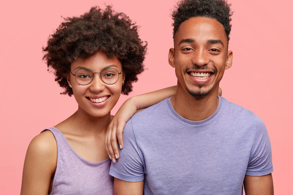 Shop Uncomfortable Revolution Empathy Gifts for Loved ones with chronic illness. Young woman and young man look straight to camera with smiles. The woman's arm rests on the shoulder of the man. They are both wearing purple tops and we can only see them from the chest up. The background is a vibrant pink hue.
