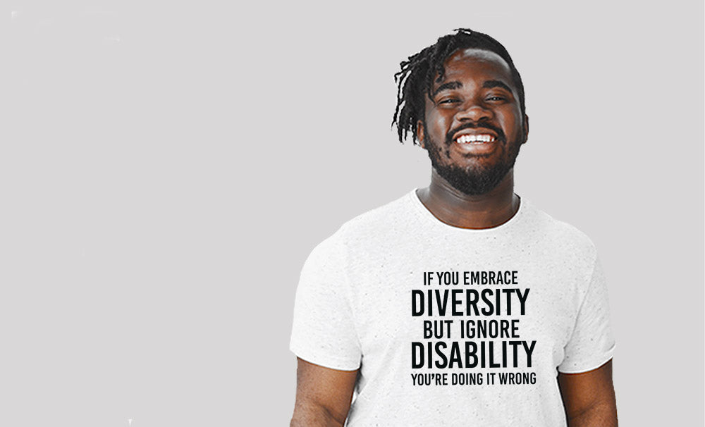 Photo of person wearing Uncomfortable Revolution Embrace Diversity T Shirt. The shirt is white with text written in all black caps: If you embrace diversity but ignore disability you're doing it wrong.