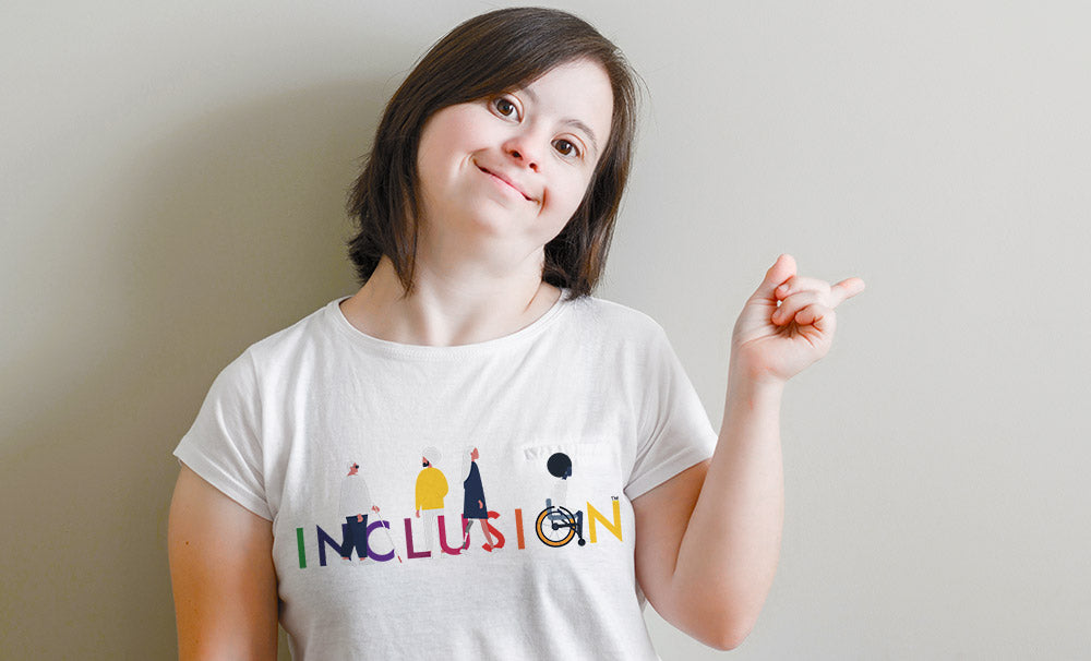 A woman model with Downs Syndrome wears an Uncomfortable Revolution Inclusion Tee-shirt in white. The Inclusion logo spells the word INCLUSION in all caps in rainbow colors. There are four characters walking among the letters: one is a plus-sized woman wearing glasses and carrying a cane. The other is a young man in a turban. The other is a female wearing a prosthetic leg. The fourth character is a woman with an afro seated in a wheelchair.