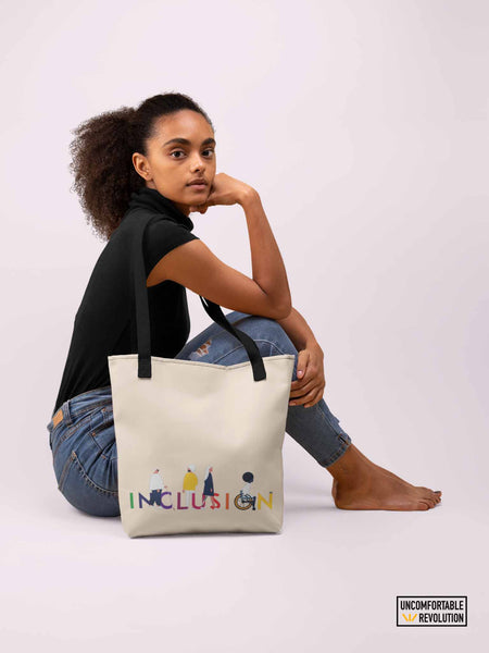 A photo of a woman of color sitting on the ground in a studio. Over her shoulder is draped URevolution's canvas inclusion tote with black straps. The inclusion tote bag has the word INCLUSION printed in rainbow-like colors on one side. Four diverse disabled people have incorporated into the word INCLUSION: a blind person, a person with an invisible illness, a disabled person with a prosthetic limb, and a disabled person in a wheelchair.