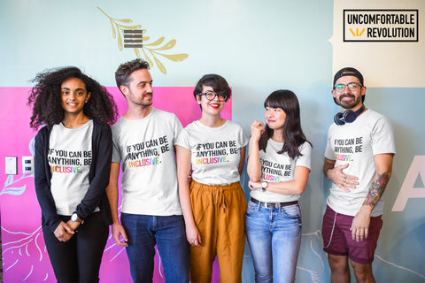 A group picture of five young people of different ethnicities wearing a URevolution unisex white Be Inclusive t-shirt with the phrase 'If you can be anything, be inclusive,' printed on it. The word INCLUSIVE is printed in the colors of the rainbow. The other words are in black.