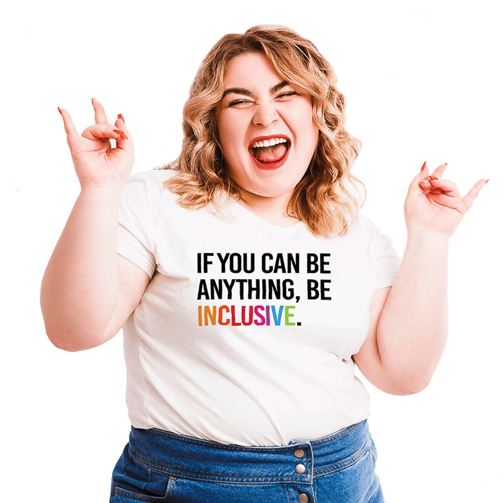 Photo of person wearing Uncomfortable Revolution Diversity and Inclusion Promotional Branding Be Inclusive T Shirt. The T shirt is white with text in all black caps that says, If you can be anything, be inclusive. The word inclusive is in rainbow colors.
