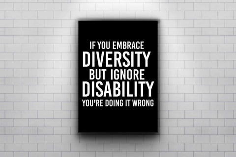 """Photo of URevolution's Embrace Diversity Poster in a subway. Poster has the phrase, """"If you embrace diversity but ignore disability, you're doing it wrong,""""  printed in white upper case letters against a black background. Poster is under a hidden spotlight mounted on a white tiled wall. This poster is only available as a custom order."""