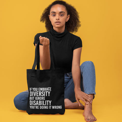 """A woman is wearing holding URevolution's disability inclusion tote bag. On the front of the black tote features our original Embrace Diversity phrase in upper case white letters: """"If you embrace diversity but ignore disability, you're doing it wrong."""""""