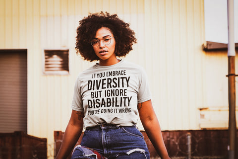 A person with an afro, tattoos, and glasses, is sitting outside in front of an old shed. They arms are open by their side. They are wearing an Embrace Diversity t-shirt with the phrase, 'If you embrace diversity but ignore disability you're doing it wrong.'