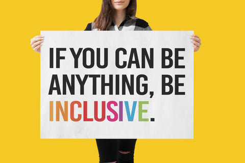 """Inclusive Posters. A person is holding a large white inclusive poster, which has the phrase """"If you can be anything, be inclusive"""" printed in black upper case letters. The word inclusive is in the colors of the rainbow."""
