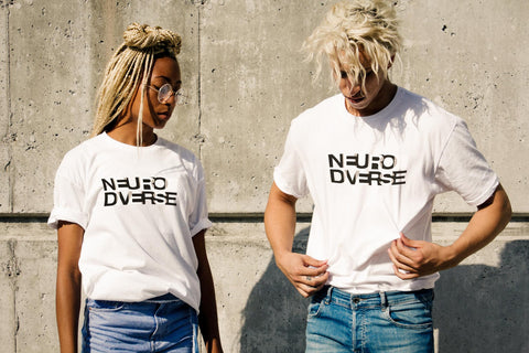 Two diverse neurodiverse people who celebrate neurodiversity by wearing original URevolution NeuroDiverse t-shirts. The white t-shirt has the text NEURODIVERSE printed in large alternating black and white letters, taking up about one-third of the surface: NEURO is printed on the top line, DIVERSE on the bottom line. The person on the left is an african-american woman in glasses with blonde braids. The person on the left is a male with blod hair in a matted dreadlock style.