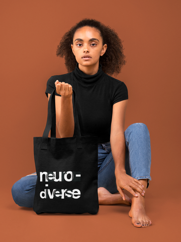 A woman is wearing holding URevolution's celebrate neurodiversity tote bag. On the front of the black bag the text NEURODIVERSE is printed in large alternating black and white letters, taking up about one-third of the surface: NEURO is printed on the top line, DIVERSE on the bottom line.