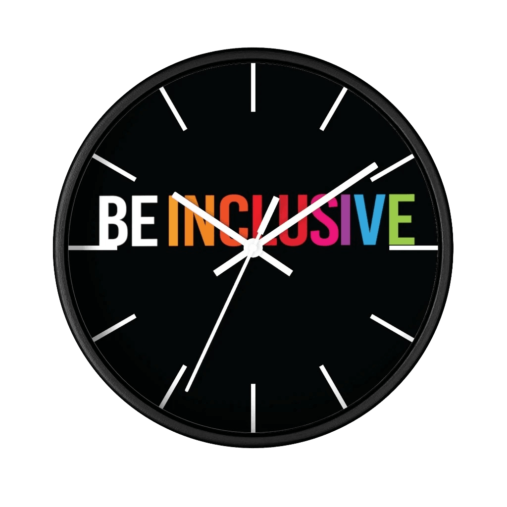 The clock has a black wooden frame and a black face. The hands are white and there are white line markers where there would ordinarily be numbers. Stretching across the face at the top are the words BE INCLUSIVE. BE is in black, and INCLUSIVE is in rainbow colors.