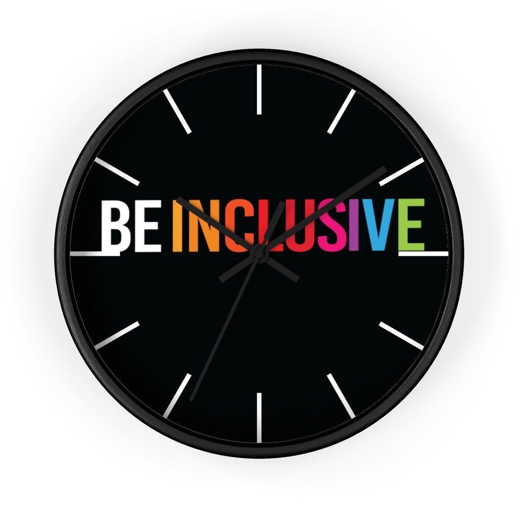 The clock has a black wooden frame and a black face. The hands are black and there are white line markers where there would ordinarily be numbers. Stretching across the face at the top are the words BE INCLUSIVE. BE is in black, and INCLUSIVE is in rainbow colors.