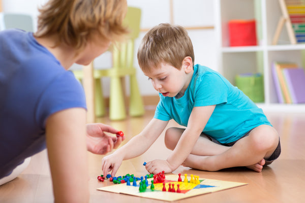 Boy playing board game with mom