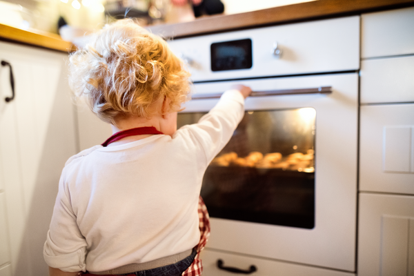 Little girl looking at the cookies in the oven.