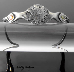 Sterling silver narrow cuff bracelet with sun emblem and cubic zirconias.