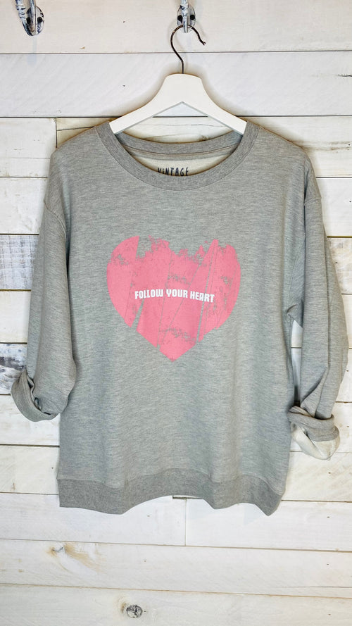 "You'll love the distressed heart design of this Follow Your Heart top. The sweatshirt style not only enhances the graphic but offers a comfortable piece to wear every day. Perfect to wear with jeans, shorts, or leggings.  Long sleeves Round neckline Ribbed neckline, cuffs, and hem Loose, oversized fit Dropped shoulders Vintage-style heart graphic print with ""Follow Your Heart"" text 94% Cotton, 4% Polyester, 2% Spandex"