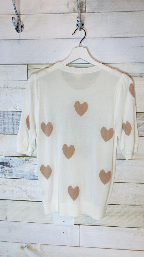 Mix and match this short sleeve heart sweater with anything in your closet. You'll love the heart pattern, the soft colors, and the short sleeves that will keep you cool on a warm day.  Short sleeves Ribbed cuffs and hem Scoop neck 100% Viscose