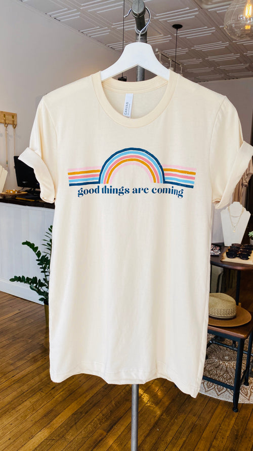 You'll love the message that this Good Things graphic tee offers because it reminds you to think positively. The printed graphic comes with a rainbow design and modern style lettering. Pair it with your favorite jeans, shorts, leggings, and more! Available in sizes S to XL  Round neckline Short sleeves Fits true to size 100% Cotton