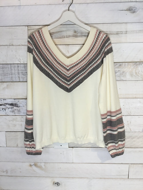 You'll love the detailing in the V-yoke of this pull-over top. The pattern creates a beautiful contrast with the cream-colored body and horizontal striped patterns on the bottom portion of the sleeves. It will look great with jeans or leggings.   V-neck Long sleeves 51% Viscose, 27% Polyester, 22% Nylon