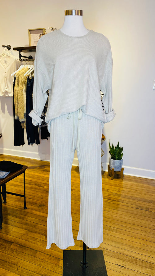 This leisure outfit is perfect for relaxing at home. The set comes with a solid top that features long sleeves. The matching drawstring pants feature a subtle striped pattern that creates a stunning contrast, with its simplicity. Pair them with your favorite sandals or shoes.   Top:  Round neck Long sleeves 95% Polyester, 5% Spandex Pants:  Elastic waist with drawstring Ribbed fabrication 95% Polyester, 5% Spandex