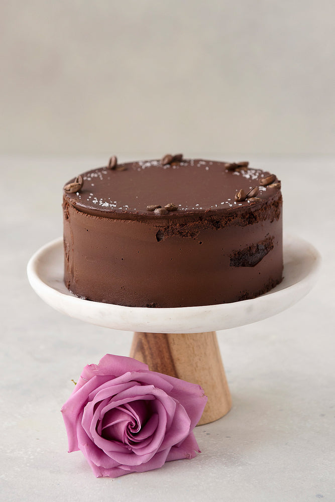 gluten free Vegan Ganache chocolate cake with vanilla sea salt and coffee bean garnish, displayed on cake stand with rose