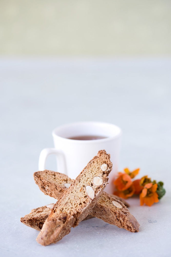 stack of 3 gluten free candied orange almond biscotti in front of cup of tea