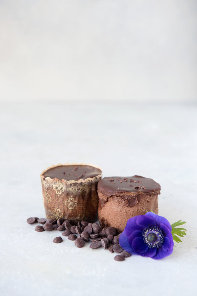Load image into Gallery viewer, 2 gluten free chocolate mini cheesecakes one in panettone wrapper one unwrapped, shown with chocolate chips & flower