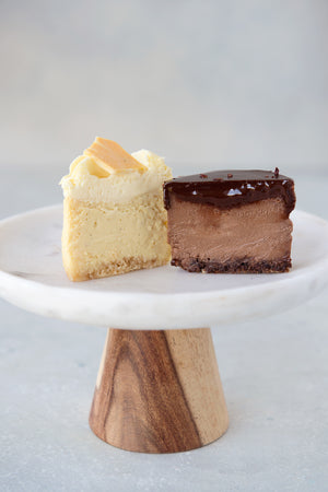 Load image into Gallery viewer, 2 halves cut face view mini gluten free cheesecakes on a cake stand, double chocolate and orange creamsicle