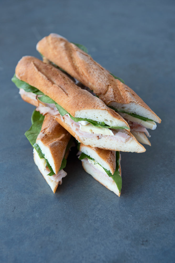 Load image into Gallery viewer, top view stack gluten free baguette sandwiches with smoked turkey brie spinach
