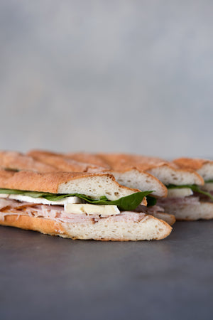 Load image into Gallery viewer, line up side view gluten free baguette sandwiches with turkey brie spinach