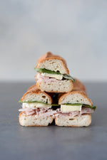 stack 3 gluten free baguette sandwiches cut face with turkey brie spinach