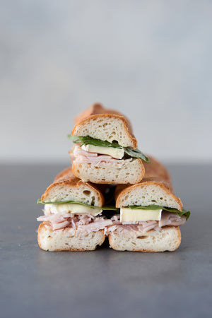 Load image into Gallery viewer, stack 3 gluten free baguette sandwiches cut face with turkey brie spinach