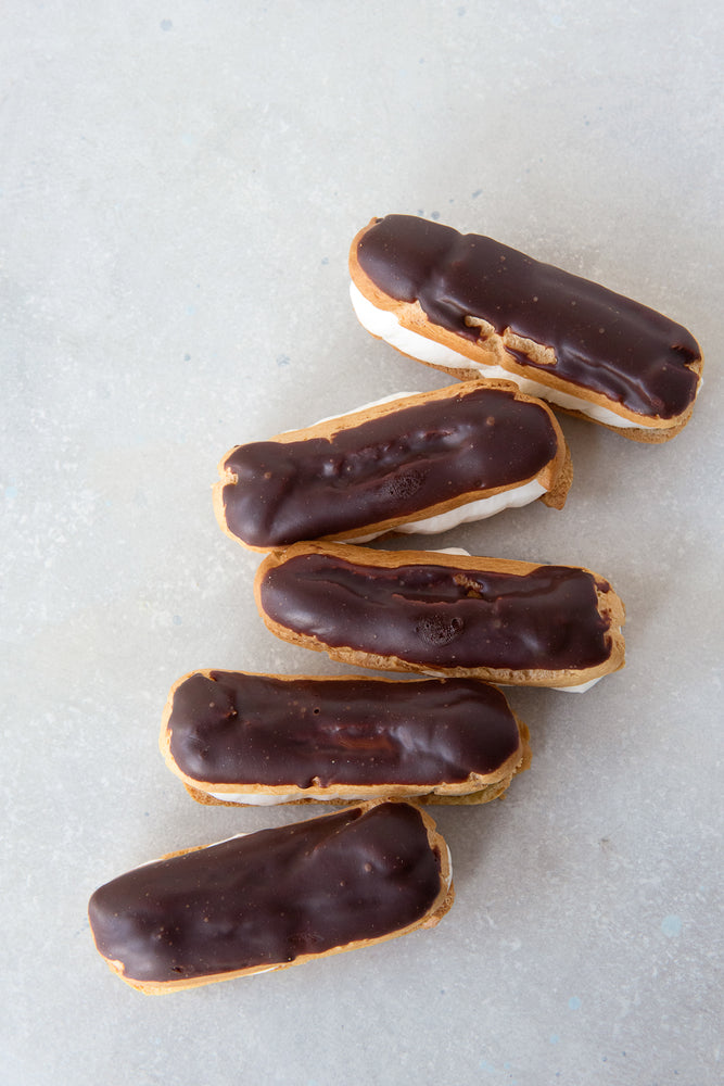 top view 5 gluten free eclairs topped with dark chocolate ganache