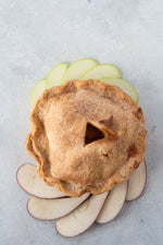 top view gluten free pie surrounded with sliced red green apples
