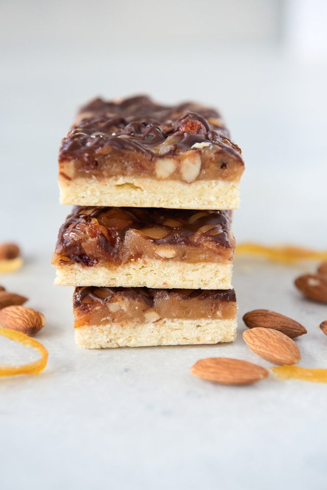 Load image into Gallery viewer, vertical stack 3 gluten free florentine bars made with caramel almonds candied citrus cranberry and chocolate drizzle on shortcrust pastry base