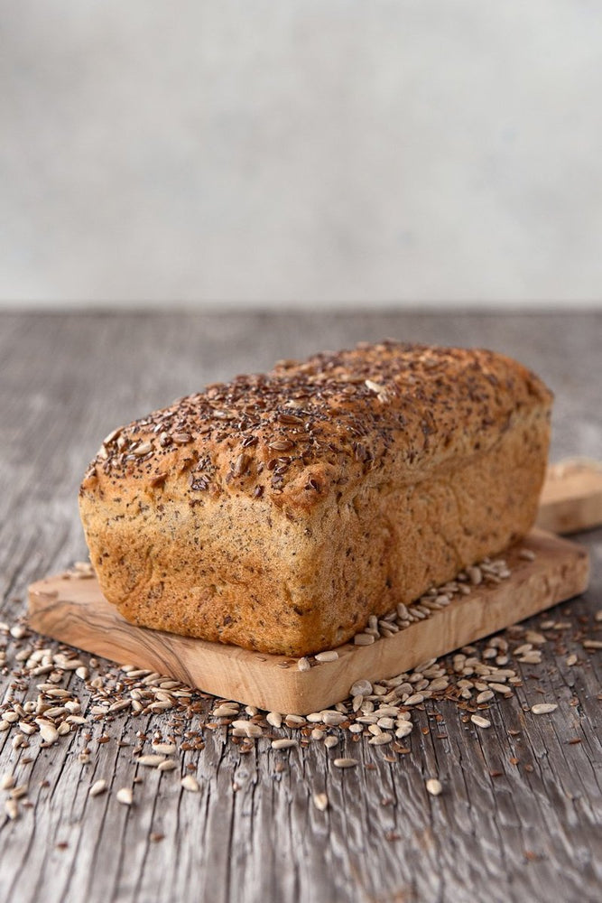 Load image into Gallery viewer, whole loaf gluten free Harvest multigrain sandwich bread on wood board, displayed with sunflower, flax and poppy seeds
