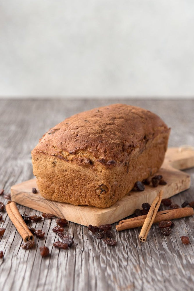 Load image into Gallery viewer, whole loaf gluten free cinnamon raisin bread on cutting board displayed with cinnamon sticks & raisins