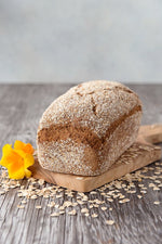 whole loaf gluten free Oat Bread on board shown with oats and flower