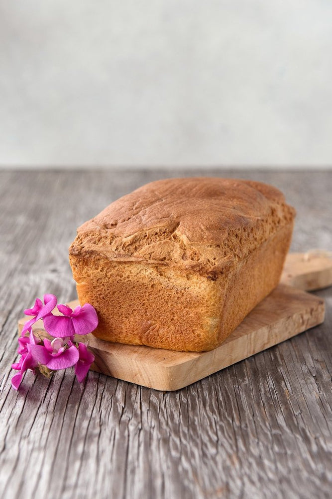 whole loaf gluten free Spring Bread on wood board with flower