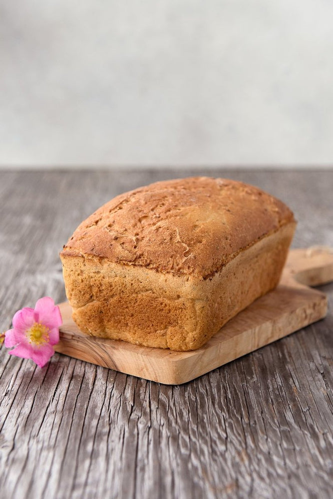 whole loaf gluten free Vega Bread on board with flower